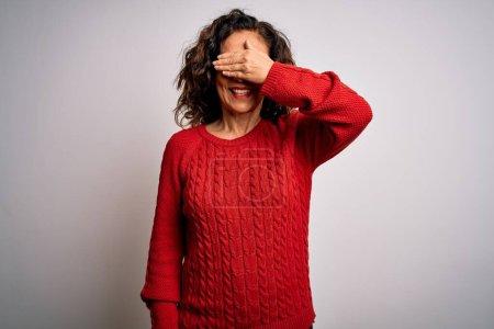 Photo pour Femme brune du moyen âge portant un pull décontracté debout sur un fond blanc isolé souriant et riant avec la main sur le visage couvrant les yeux pour la surprise. Concept aveugle. - image libre de droit