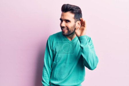 Photo for Young handsome man with beard wearing casual sweater smiling with hand over ear listening and hearing to rumor or gossip. deafness concept. - Royalty Free Image