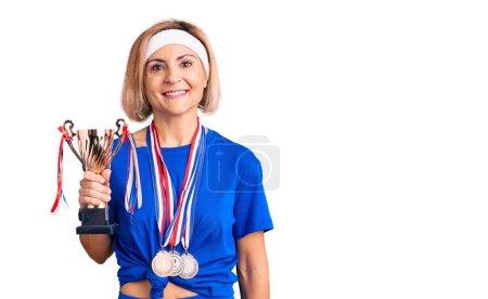 Photo pour Jeune femme blonde tenant trophée champion portant des médailles regardant positif et heureux debout et souriant avec un sourire confiant montrant les dents - image libre de droit