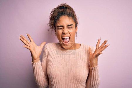 Photo pour Jeune belle fille afro-américaine portant un pull décontracté debout sur fond rose célébrant fou et fou de succès avec les bras levés et les yeux fermés hurlant excités. Concept gagnant - image libre de droit