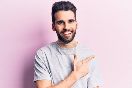 Photo for Young handsome man with beard wearing casual t-shirt smiling cheerful pointing with hand and finger up to the side - Royalty Free Image