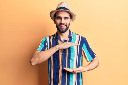 Photo for Young handsome man with beard wearing summer hat and shirt gesturing with hands showing big and large size sign, measure symbol. smiling looking at the camera. measuring concept. - Royalty Free Image