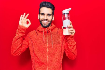 Foto de Joven hombre guapo con barba usando ropa deportiva bebiendo botella de agua haciendo signo ok con los dedos, sonriendo gesto amistoso excelente símbolo - Imagen libre de derechos