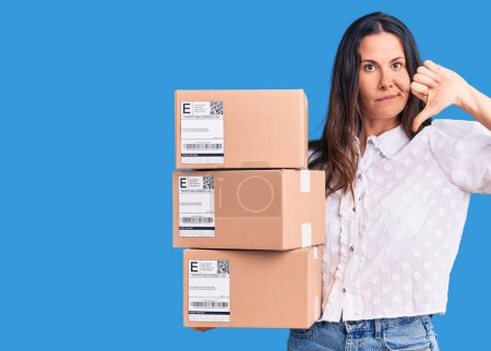 Photo for Young beautiful brunette woman holding delivery cardboard package with angry face, negative sign showing dislike with thumbs down, rejection concept - Royalty Free Image
