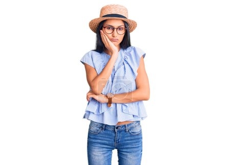 Photo for Young beautiful latin girl wearing summer hat and glasses thinking looking tired and bored with depression problems with crossed arms. - Royalty Free Image