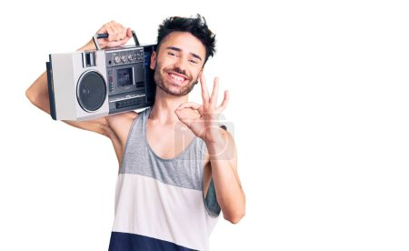 Photo for Young hispanic man holding boombox, listening to music doing ok sign with fingers, smiling friendly gesturing excellent symbol - Royalty Free Image