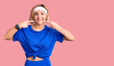 Photo for Young blonde woman wearing sportswear smiling cheerful showing and pointing with fingers teeth and mouth. dental health concept. - Royalty Free Image