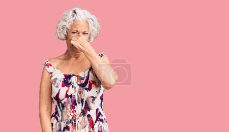 Photo for Senior grey-haired woman wearing casual clothes smelling something stinky and disgusting, intolerable smell, holding breath with fingers on nose. bad smell - Royalty Free Image
