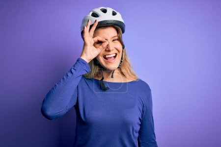 Photo for Young beautiful blonde cyclist woman wearing bike security helmet over purple background doing ok gesture with hand smiling, eye looking through fingers with happy face. - Royalty Free Image
