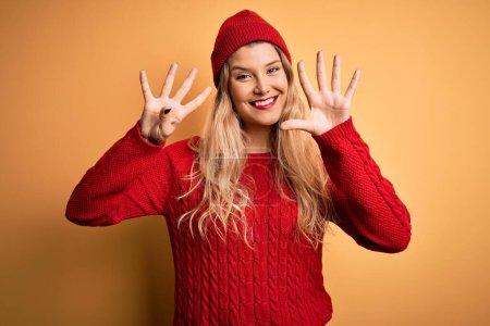 Photo pour Jeune belle femme blonde portant pull décontracté et bonnet de laine sur fond blanc montrant et pointant vers le haut avec les doigts numéro neuf tout en souriant confiant et heureux. - image libre de droit