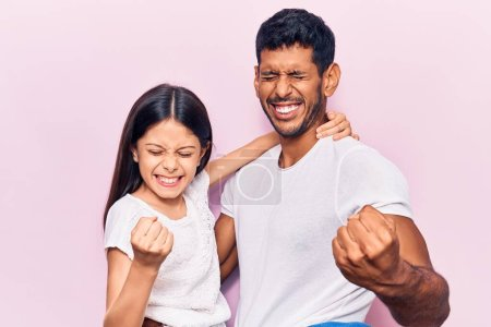 Photo for Young father and daughter wearing casual clothes excited for success with arms raised and eyes closed celebrating victory smiling. winner concept. - Royalty Free Image