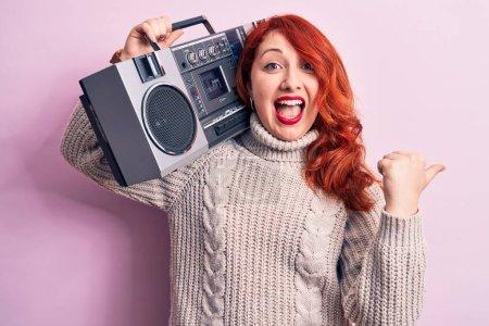 Photo pour Belle rousse femme écoutant de la musique tenant boombox vintage sur fond rose pointant le pouce vers le côté souriant heureux avec bouche ouverte - image libre de droit
