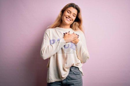 Photo pour Jeune belle femme blonde portant un pull décontracté debout sur fond rose souriant avec les mains sur la poitrine avec les yeux fermés et geste reconnaissant sur le visage. Concept de santé. - image libre de droit