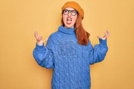 Photo pour Jeune belle femme rousse portant béret français et des lunettes sur fond jaune fou et fou crier et crier avec expression agressive et les bras levés. Concept de frustration. - image libre de droit