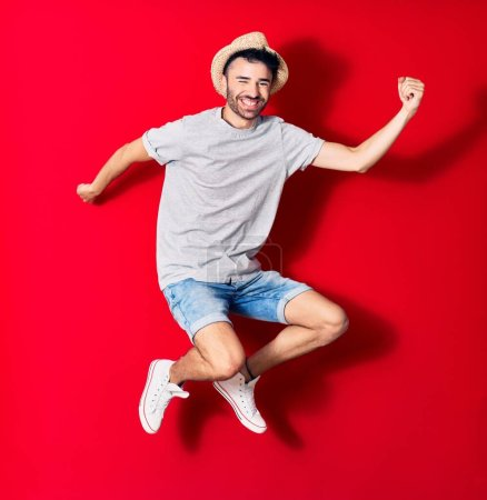 Photo for Young handsome hispanic man wearing casual clothes and summer hat smiling happy. Jumping with smile on face celebrating with fists up over isolated red background. - Royalty Free Image