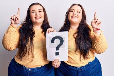 Photo pour Jeunes jumeaux plus la taille tenant le point d'interrogation surpris par une idée ou une question pointant du doigt avec le visage heureux, numéro un - image libre de droit