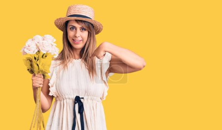 Young beautiful woman wearing hat holding bouquet of flowers pointing finger to one self smiling happy and proud