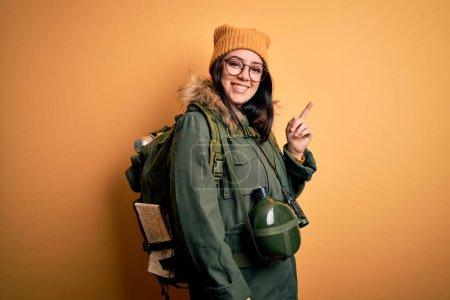 Photo pour Jeune randonneuse portant un sac à dos de randonnée, une cantine et une carte sur fond jaune avec un grand sourire sur le visage, pointant la main et le doigt vers le côté en regardant la caméra. - image libre de droit