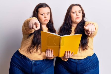 Photo for Young plus size twins holding book pointing with finger to the camera and to you, confident gesture looking serious - Royalty Free Image