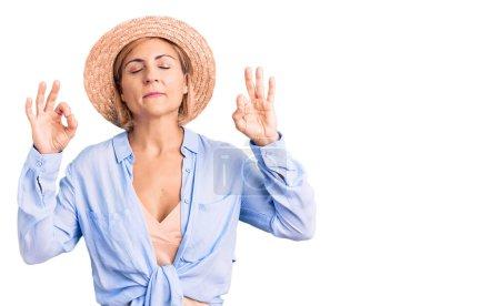 Photo pour Jeune femme blonde portant un chapeau d'été se détendre et sourire les yeux fermés en faisant un geste de méditation avec les doigts. concept de yoga. - image libre de droit