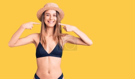 Photo for Young beautiful girl wearing bikini and hat smiling cheerful showing and pointing with fingers teeth and mouth. dental health concept. - Royalty Free Image