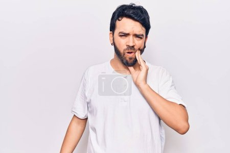 Photo for Young hispanic man wearing casual clothes touching mouth with hand with painful expression because of toothache or dental illness on teeth. dentist - Royalty Free Image
