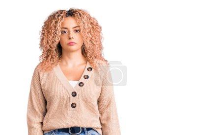 Photo pour Jeune femme blonde aux cheveux bouclés portant un pull d'hiver décontracté détendu avec une expression sérieuse sur le visage. simple et naturel regardant la caméra. - image libre de droit