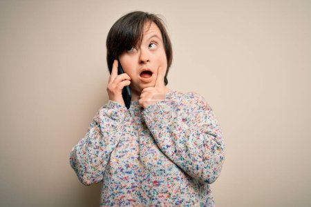 Photo pour Jeune femme trisomique ayant une conversation parlant sur smartphone visage sérieux penser à la question, idée très confuse - image libre de droit