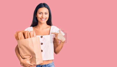 Photo for Young beautiful latin girl holding paper bag with bread pointing finger to one self smiling happy and proud - Royalty Free Image