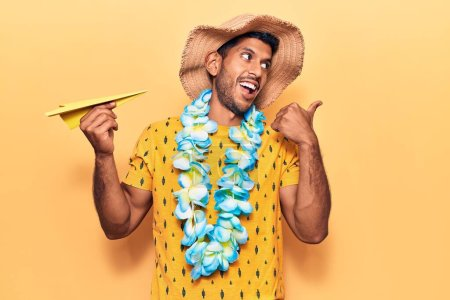 Photo for Young latin man wearing summer hat and hawaiian lei holding paper airplane pointing thumb up to the side smiling happy with open mouth - Royalty Free Image
