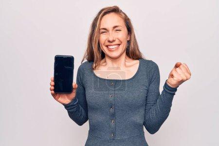 Photo pour Jeune belle femme blonde montrant écran de smartphone criant fier, célébrant la victoire et le succès très excité avec le bras levé - image libre de droit