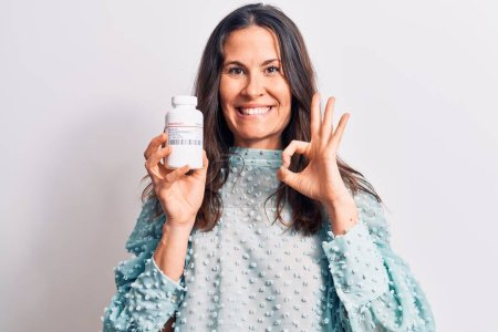 Photo for Young beautiful brunette woman holding jar of medicine pills over isolated white background doing ok sign with fingers, smiling friendly gesturing excellent symbol - Royalty Free Image