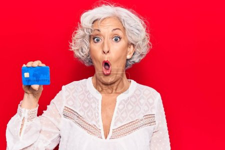 Photo for Senior grey-haired woman holding credit card scared and amazed with open mouth for surprise, disbelief face - Royalty Free Image