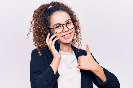 Photo pour Belle fille enfant avec les cheveux bouclés portant des lunettes ayant conversation parler sur le smartphone souriant heureux et positif, pouce levé faire excellent et signe d'approbation - image libre de droit