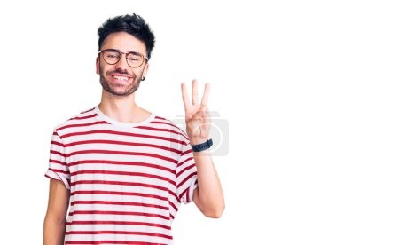 Photo for Young hispanic man wearing casual clothes showing and pointing up with fingers number three while smiling confident and happy. - Royalty Free Image
