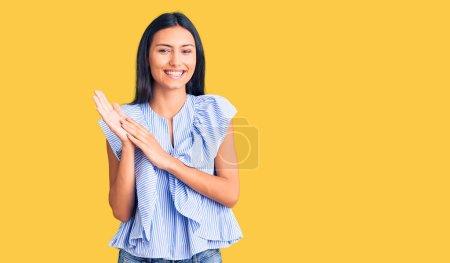 Photo pour Jeune belle fille latine portant des vêtements décontractés applaudissant et applaudissant heureux et joyeux, souriant mains fières ensemble - image libre de droit