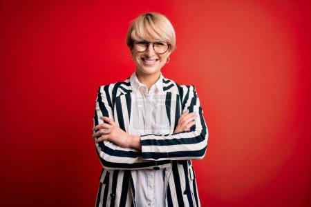 Photo pour Femme d'affaires blonde aux cheveux courts portant des lunettes et veste rayée sur fond rouge heureux visage souriant avec les bras croisés regardant la caméra. Personne positive. - image libre de droit