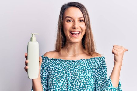 Photo for Young beautiful girl holding bottle of cream lotion pointing thumb up to the side smiling happy with open mouth - Royalty Free Image