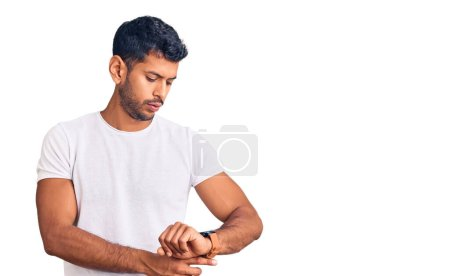 Photo for Young latin man wearing casual clothes checking the time on wrist watch, relaxed and confident - Royalty Free Image