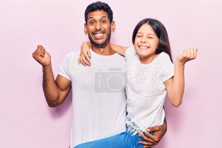 Photo for Latin father and daughter wearing casual clothes screaming proud, celebrating victory and success very excited with raised arm - Royalty Free Image
