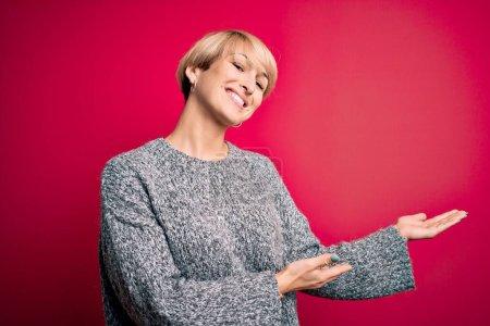 Photo pour Jeune femme blonde aux cheveux courts modernes portant un pull décontracté sur fond rose Invitant à entrer souriant naturel à la main ouverte - image libre de droit
