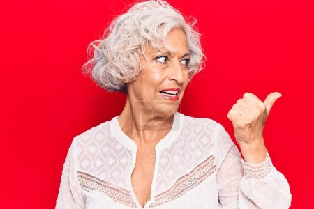 Photo for Senior grey-haired woman wearing casual clothes pointing thumb up to the side smiling happy with open mouth - Royalty Free Image