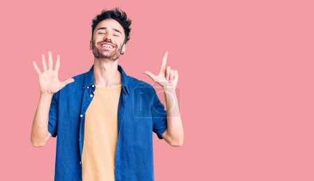 Photo for Young hispanic man wearing casual clothes showing and pointing up with fingers number seven while smiling confident and happy. - Royalty Free Image