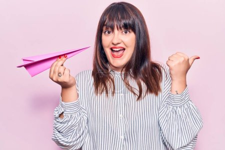 Photo pour Young plus size woman holding paper airplane pointing thumb up to the side smiling happy with open mouth - image libre de droit