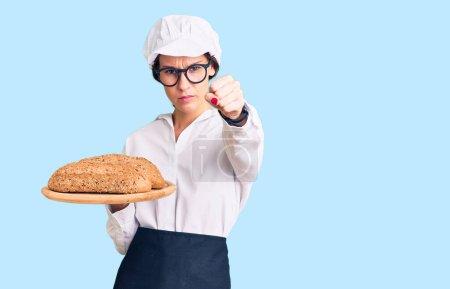 Photo pour Belle brune jeune femme portant un uniforme de boulanger tenant du pain fait maison ennuyée et frustrée criant de colère, criant folle de colère et la main levée - image libre de droit