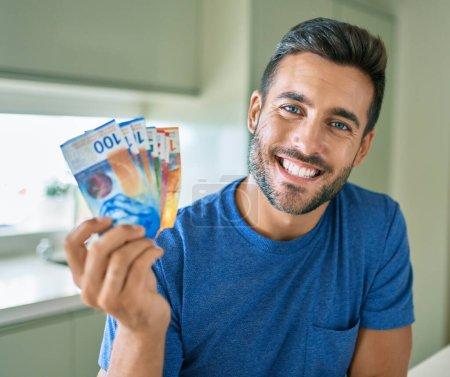 Photo pour Jeune homme beau sourire heureux tenant des billets en francs suisses à la maison - image libre de droit