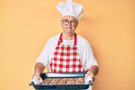 Photo pour Senior homme aux cheveux gris portant uniforme boulanger tenant biscuits faits maison clin d'oeil en regardant la caméra avec une expression sexy, gai et heureux visage. - image libre de droit