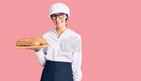 Photo pour Belle brune jeune femme portant un uniforme de boulanger tenant du pain fait maison regardant positif et heureux debout et souriant avec un sourire confiant montrant des dents - image libre de droit