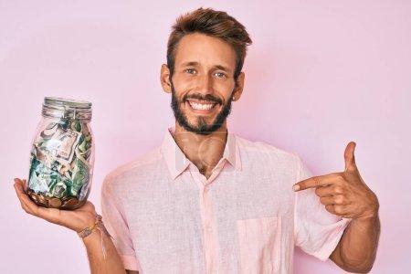 Photo pour Bel homme caucasien avec barbe tenant pot avec des économies pointant du doigt à un sourire heureux et fier - image libre de droit
