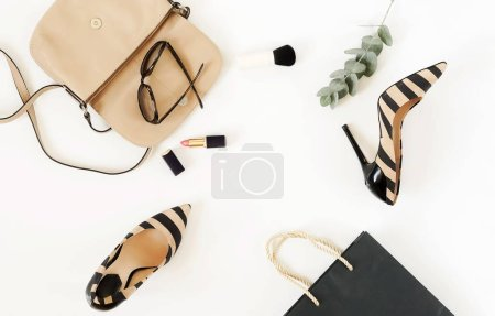 Photo for Flat lay, top view of female fashion accessories.Beige handbag, sunglasses, high heel shoes and cosmetics on white background. Copy space - Royalty Free Image